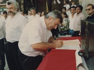 Un representante de la Cofradía de Remo firma un escrito en el que refleja la cesión por parte de dicha Cofradía al Ayuntamiento de Pasaia de un mural dedicado a los remeros y colocado en la plaza Santiago
