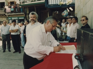 Un representante de la Cofradía de Remo firma un escrito que refleja la cesión por parte de dicha Cofradía al Ayuntamiento de Pasaia de un mural dedicado a los remeros y colocado en la plaza Santiago