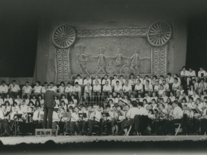 Homenaje a Usandizaga en el centenario de su nacimiento y Cincuentenario del Bombardeo de Gernika : concierto de la Orquesta de Pasaia frente a un lienzo que representa un grupo de figuras bailando al son de la txirula y el tambor