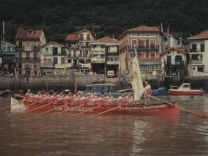 Remeros del Donibaneko, campeones de la regata de la Concha de San Sebastián, bogan con la bandera en manos del patrón
