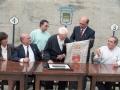 Actos de homenaje al sacristán de Zubillaga. A la derecha Eli Galdos le hace entrega de la bandera de Oñati y a la izquierda del homenajeado se encuentra Imanol Murua