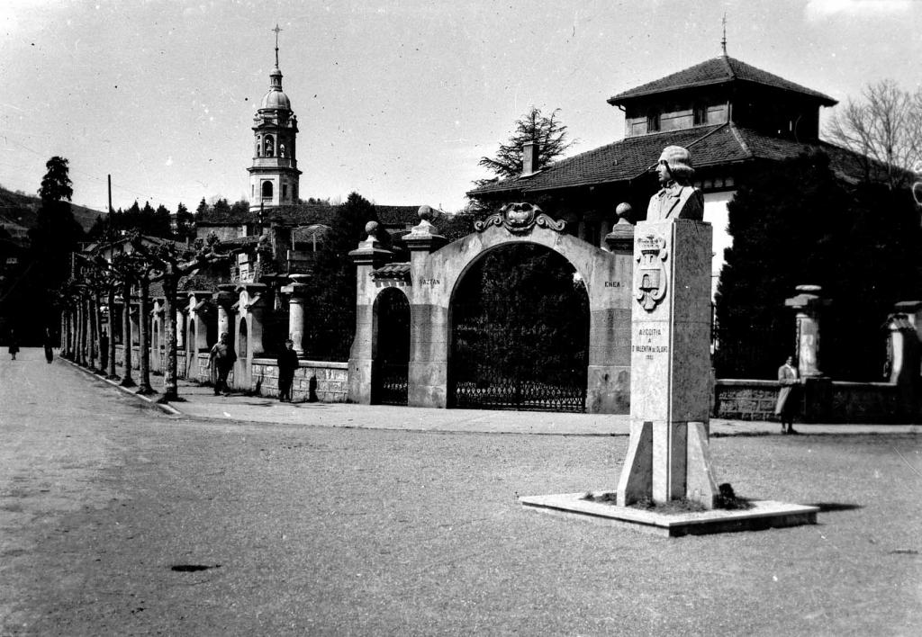 """Azcoitia. Estatua de Olano y la Torre de la Iglesia Parroquial al fondo"""