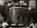 Carroza de la tamborrada infantil, con forma de tambor y txistu, en la plaza de los Fueros. Sobre la carroza van montados varios niños vestidos de baserritarras
